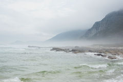 Ocean against the misty mountains Royalty Free Stock Photo