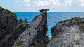 Ocean Błękitny Nawadnia z czarnego Skalistej plaży niebieskiego nieba białymi chmurami w horyzoncie Zdjęcie Royalty Free