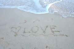 Sea waves on the clean beach with a word of Love on the sand stock photography