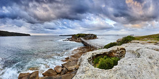 Ocean Bare Rise Hole Pan. AUstralia Pacific ocean coast near Sydney Bare island wooden bridge at the entrance to Botany Bay at sunrise panoramic view over sand Stock Images