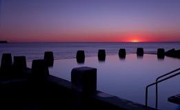 Dawn Ocean Sunrise Swimming Pool Bath Silhoutte. Sunrise over ocean tidal pool bath Stock Photo