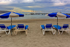 Ocean beach with chairs in Los Cristianos city. Tenerife. Royalty Free Stock Image
