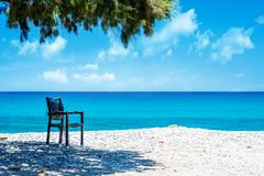 Ocean beach on the Crete. Ocean beach and chair on the Crete in sunny day Stock Photography