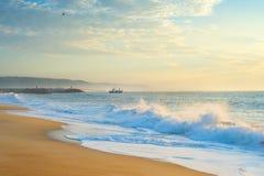 Ocean beach fishing ship Portugal. Landscape with the ocean beach, fishing ship at beautiful sunset. Nazare, Portugal stock photos