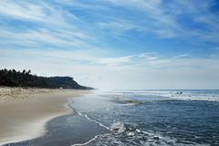 The ocean beach is in the horizon with small waves and haze. Royalty Free Stock Photo