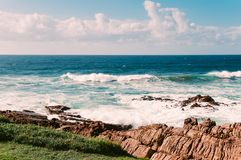 Ocean beach in Margate, SA, blue sky, white clouds, turquoise waves, rocks. Ocean beach in Margate, South Africa, blue sky, white clouds, turquoise waves, rocks Royalty Free Stock Image
