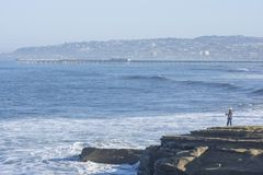 Ocean Beach pier and man fishing on rocky shore. Beautiful coastline of Ocean Beach in San Diego, California with pier and man surf fishing from rocky shore on Stock Photography