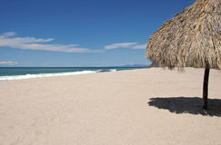 Ocean, beach, sand and palapa Stock Photography