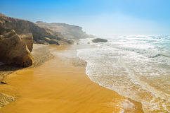 Ocean beach in summer under blue sky. Waves lapping on rocky shore Stock Images