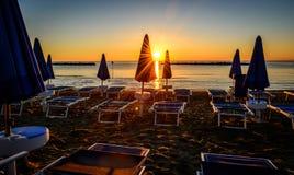 Ocean beach at sunrise. Ocean beach with blue beach umbrella at sunrise Stock Photo