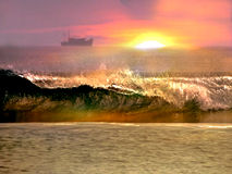 Ocean and beach sunset scene. The sun setting over the ocean as seen from a beach. The waves are crashing and reflecting sunlight Stock Photos