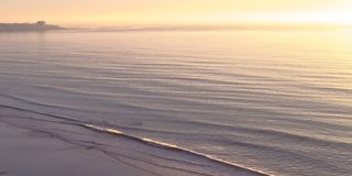 Ocean at Blacks Beach with sunset in the horizon. A view of the Pacific Ocean at Blacks Beach in San Diego, California. The water glistens under the light of royalty free stock photo