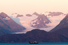 Ocean Boat and Snowy Mountains on Sunset. A boat motors through a protected part of the North Pacific Ocean underneath a massive mountain range. A huge glacier Royalty Free Stock Image
