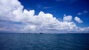 The ocean with bright blue skies and white clouds. Landscape view of the ocean with bright blue skies and white clouds. Small islands are also visible in the Stock Photos