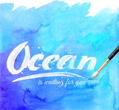Ocean calligraphy sign on blue watercolor Royalty Free Stock Images