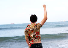 Ocean cheer. A young man raising his right arm with fist facing the ocean Royalty Free Stock Photography