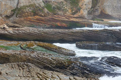 Ocean cliff with waves and bright striped coastal rocks Royalty Free Stock Photo