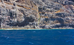 Ocean cliffs. Steep rocky volcanic cliffs near ocean Stock Photos