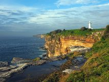 Ocean Cliffs With a White Lighthouse. A white lighthouse on an oceanside sandstone cliff, with water filled rock pool, on a cloudy morning. While this is a Royalty Free Stock Image