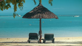 Ocean coast with chaise longues and sun umbrella. Summer vacation scene. Empty chaise longues under straw sun umbrella on the ocean coast. Beach with white sand stock video footage