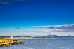 Ocean coast lighthouse in Port Charlotte, Scotland Stock Images