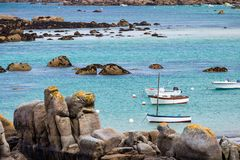 Ocean coast in Meneham village with granite rocks and boats, Kerlouan, Finistere, Brittany (Bretagne), France stock image