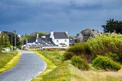 Ocean coast in Meneham village with granite rocks and boats, Kerlouan, Finistere, Brittany Bretagne, France.  stock image