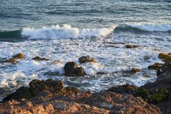 Ocean coast with rocks and waves at sunrise. Beautiful seascape.  royalty free stock image