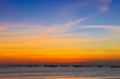 Ocean coast sunset and fishing boats Stock Images