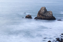 Ocean coastal rocks at evening with blurred waves Stock Photo