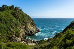 Ocean Cove. Surrounded by grassy mountains stock image