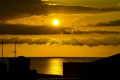 Ocean at dawn. Photo of the sea at sunrise with silhouettes of houses royalty free stock images