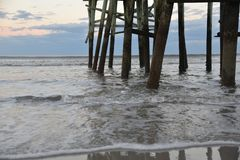 The pier experiences the waves crashing into the pilings all day and night stock images