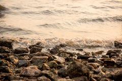 Ocean fala przeciw skałom Denna fala uderzeniowej piana na otoczaka kamienia plaży Wody morskiej pluśnięcie fala na kamiennym pla Fotografia Stock