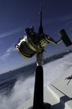 Ocean fishing. Atlantic ocean fishing with rod and reel in holder in boat with waves splashing out Stock Photography