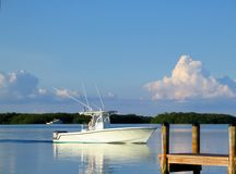 Ocean Fishing Boat out on the bay nearing dock with reflection o royalty free stock photography