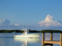 Ocean Fishing Boat out on the bay. Nearing dock with reflection on calm water and beautiful clouds and sky royalty free stock photo
