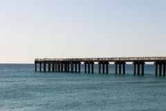 Ocean fishing pier stretchs over calm seas Stock Photography