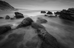 Ocean flowing over rocks. Ocean flowing over rock at Victoria Bay on the Garden Route in black and white long exposure Stock Photo