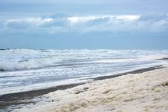 Ocean foam on sand beach during mild sea storm with waves in background in Europe stock photo
