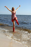 Ocean fun. A pretty girl wearing a sundress and rubber boots splashing in the ocean royalty free stock images
