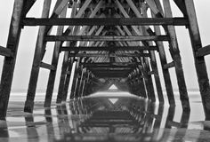 Ocean Gate. A very old pier with its reflection on the beach royalty free stock photos
