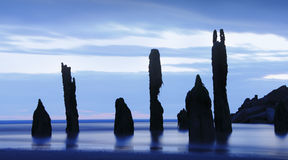 Ocean ghosts sunset. Ocean ghosts, silhouette weathered beach posts at sunset Stock Image