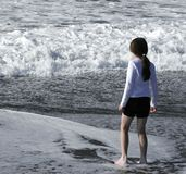 Ocean Girl. A young girl watches the surf Stock Image