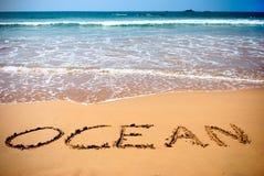 Ocean handwritten inscription in sand Stock Photography
