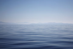 Ocean with hazy mountain shore Royalty Free Stock Photos