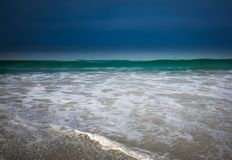 Green Ocean with Dark Blue Storm and Sun on Foam. Ocean Horizon in Dark Blue, Green and White Stock Image