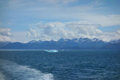 Ocean, iceberg, mountains and clouds. Royalty Free Stock Photo
