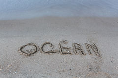 Ocean. Inscription `Ocean` in the sand on the beach Stock Photography