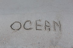 Ocean. Inscription `Ocean` in the sand on the beach Royalty Free Stock Photo